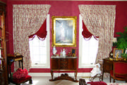 Master bedroom drapes in red and cream toile with balloon shades trimmed with tassels