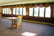 The dining room window treatment are floral swags and cascades to help the residence feel at home.