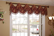 Swaged valance with tassel fringe on antique gold wood rod compliment paint color in the dining room.