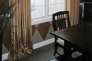 Terra-cotta and gold faux silk drapery panels mounted on wrought iron rod