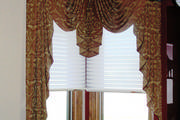 Corner window treatment with swags and cascades in a jacquard fabric with micro piping in red.