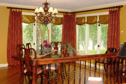 Floor length drapes in a beautiful brocade with golden silk roman shades frame the dining room corner windows.