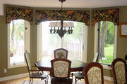 Kitchen bay window with arched cornices in a tropical print with a black background.