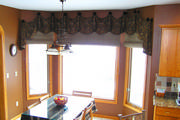 For this arched window a roman shades was used along with a draped valance in brown and gold paisley.