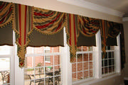 Striped swags and cascades with tassel trim over coordinating roller shades.