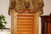 Golden swagged valance with tassel trim softens the look of the plantation shutters.