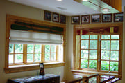 Antique wooden oars attached to cedar cornices with linen roman shades add to the rustic feel of the room.